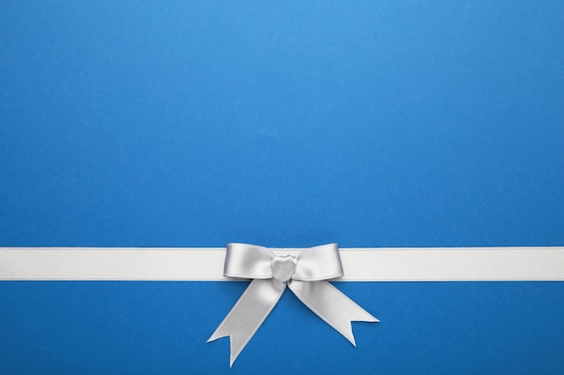 Fita prateada e laço na superfície azul pastel