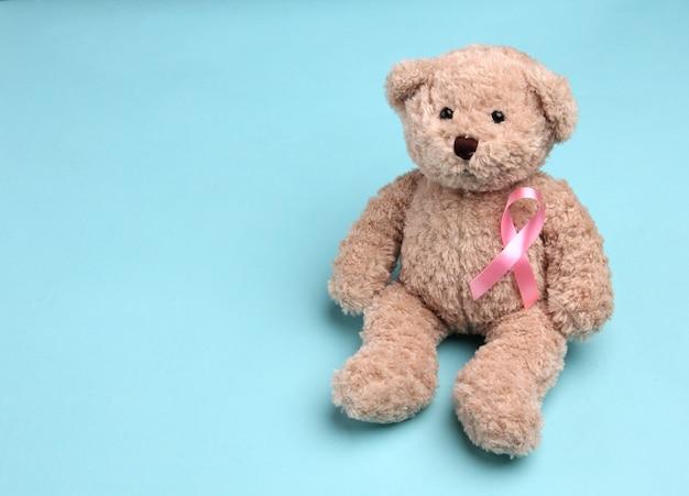 Fita rosa de urso de pelúcia sobre fundo azul.