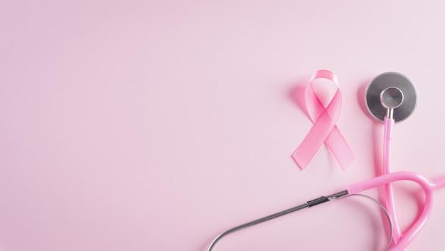 Fita rosa e estetoscópio sobre fundo rosa pastel símbolo da conscientização sobre o câncer de mama feminino