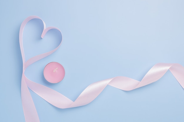 Fita rosa em forma de coração e uma vela rosa sobre fundo azul. lugar para texto. conceito de dia dos namorados.