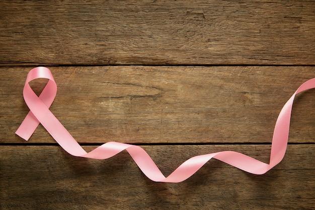 Fita rosa no conceito de fundo de conscientização do câncer de mama de madeira
