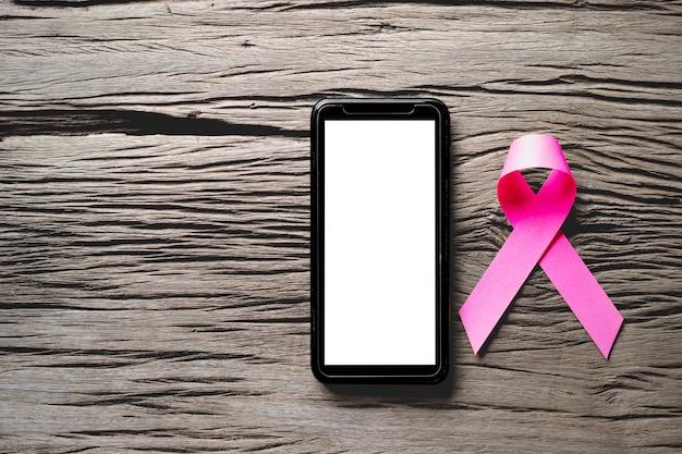 Fita rosa para o dia da campanha contra o câncer de mama e smartphone de tela em branco.