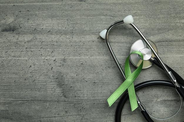 Fita verde de conscientização e estetoscópio em plano de fundo texturizado cinza