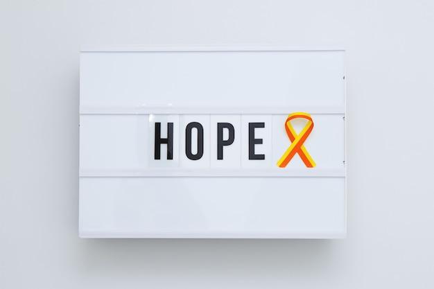 Fita vermelha-amarela como conscientização do símbolo do dia mundial da hepatite na mesa de luz