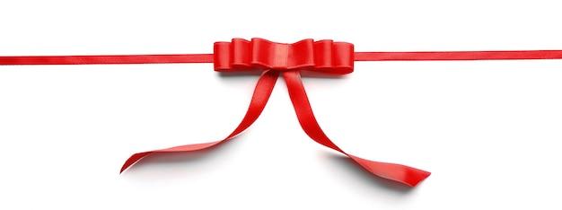 Fita vermelha brilhante com laço isolado no branco