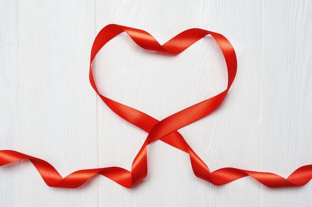 Fita vermelha com forma de coração no fundo branco de madeira para cartão de dia dos namorados