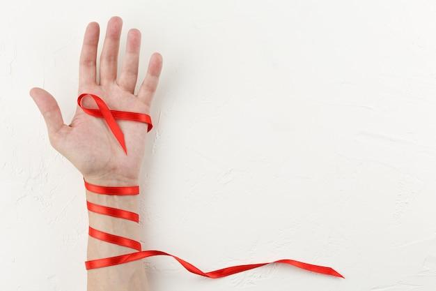 Fita vermelha de câncer enrolada no braço