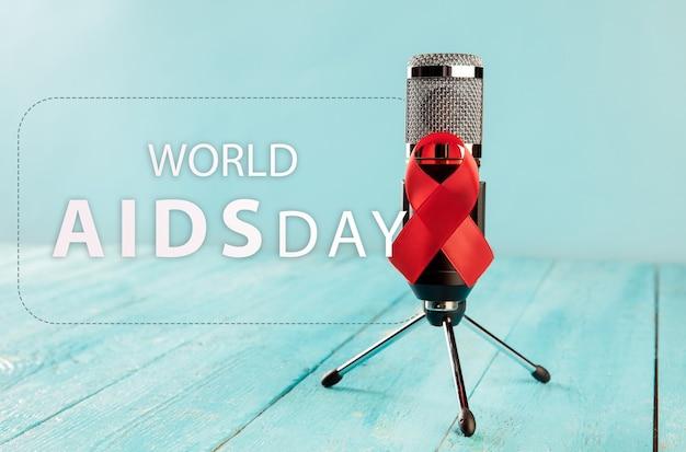 Fita vermelha de sinal de conscientização contra a aids com microfone no piso de madeira
