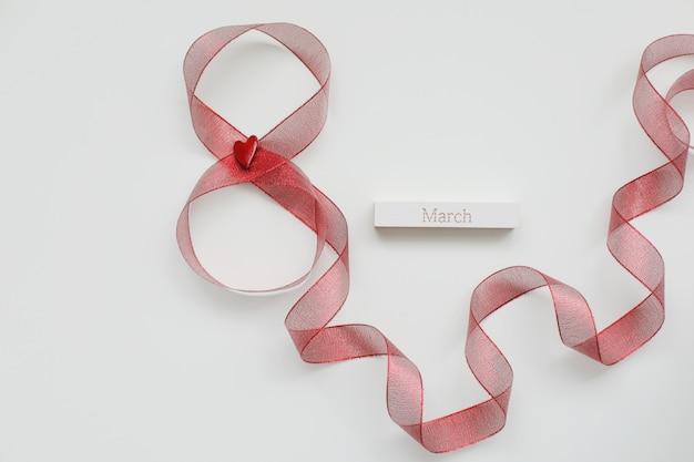 Fita vermelha e palavra março em fundo branco. 8 de março, conceito do dia internacional da mulher.