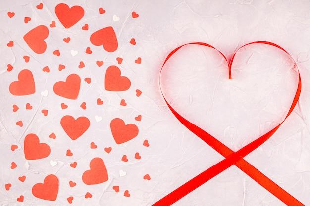 Fita vermelha em forma de coração e corações de papel confete em concreto cinza