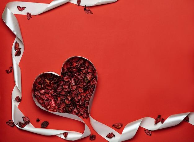 Fita vermelha em forma de coração e pétalas de rosa para o dia dos namorados.