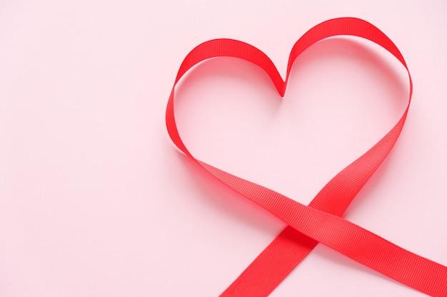 Fita vermelha em forma de coração em fundo rosa