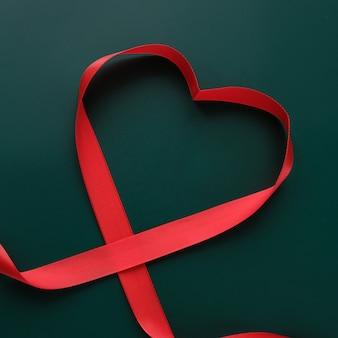 Fita vermelha em forma de coração em fundo verde escuro