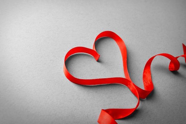 Fita vermelha em forma de coração em plano de fundo texturizado claro