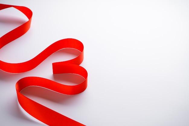 Fita vermelha em forma de coração em um fundo branco com lugar para texto.