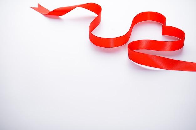 Fita vermelha em forma de coração em um fundo branco. dia dos namorados. conceito de amor. com lugar para texto