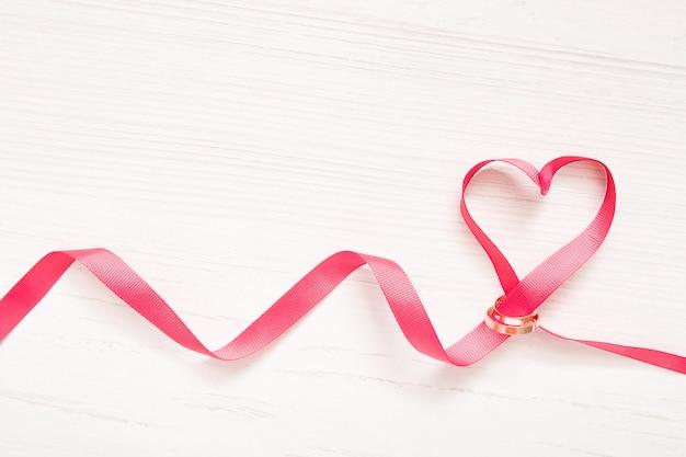 Fita vermelha em forma de coração enfiada em alianças de casamento