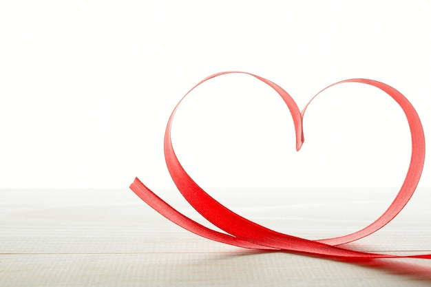 Fita vermelha em formato de coração na mesa