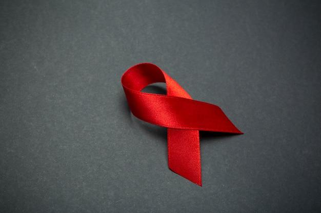 Fita vermelha sobre um fundo cinza escuro. símbolo do dia mundial da aids ou mês de conscientização sobre câncer ou hiv e conceito de cuidados de saúde. copie o espaço