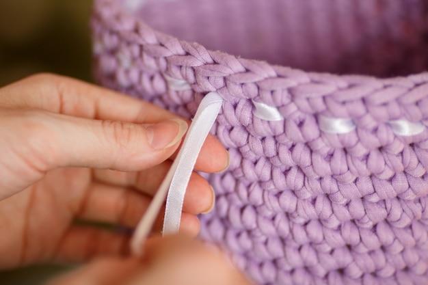 Fita vestindo da mulher entre o weave de cesta do fio para confecção de malhas. fechar-se