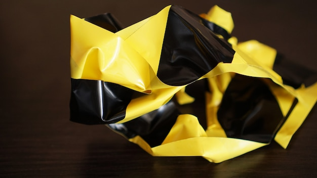 Fitas amarelas e pretas amassadas em fundo escuro