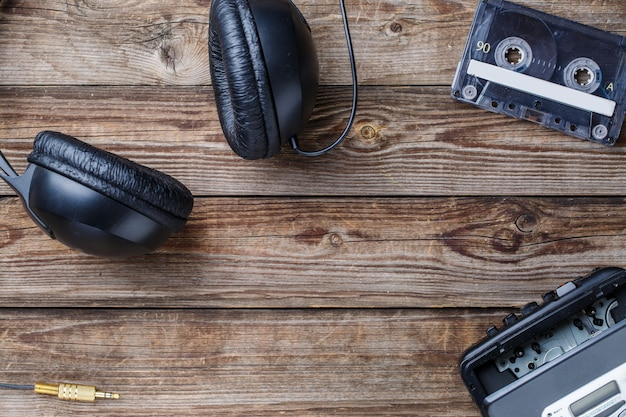 Fitas cassete, toca-fitas e fones de ouvido sobre a mesa de madeira. vista do topo. conceito retrô com espaço vazio para texto, logotipo, etc.