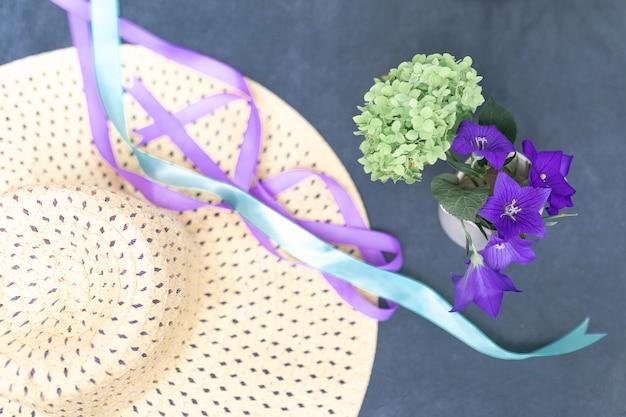 Fitas de chapéu de palha feminino e um pequeno buquê de hortênsias verdes e sinos