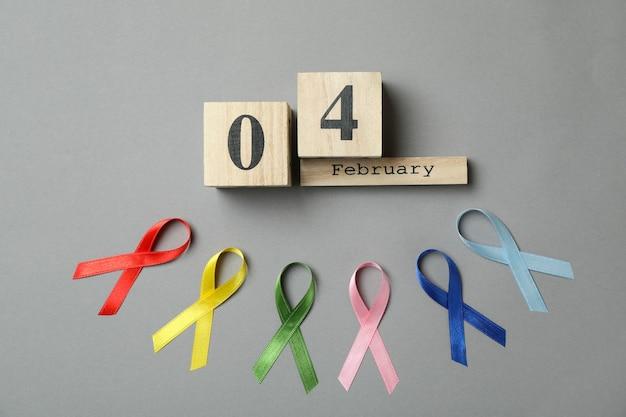 Fitas de conscientização multicoloridas e calendário com 4 de fevereiro em cinza