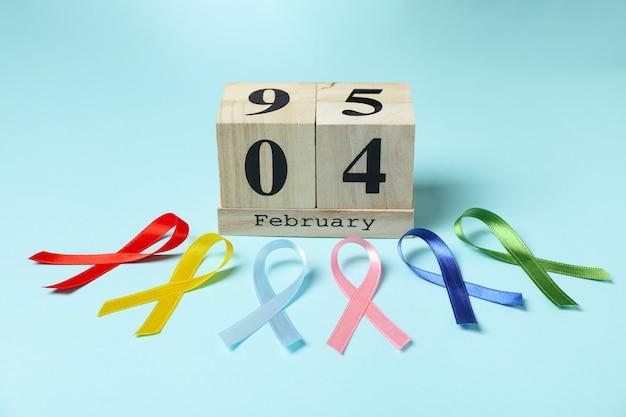 Fitas de conscientização multicoloridas e calendário com 4 de fevereiro em fundo azul