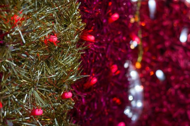 Fitas de guirlanda dourada e rosa com fundo de luzes vermelhas e brancas decoração colorida de natal