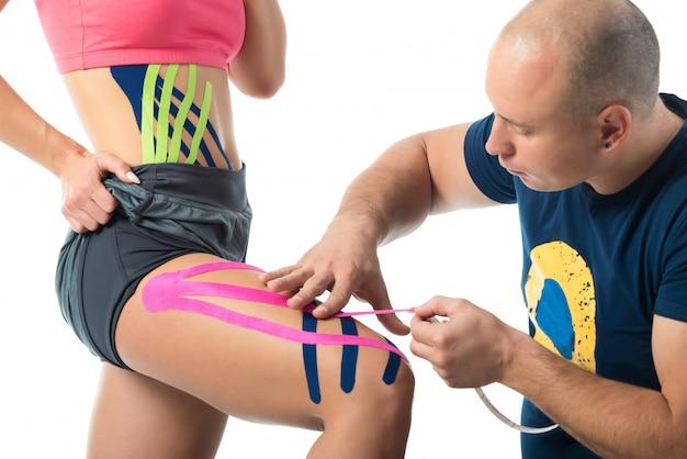 Fitas de kinesio da vara do terapeuta na perna da mulher