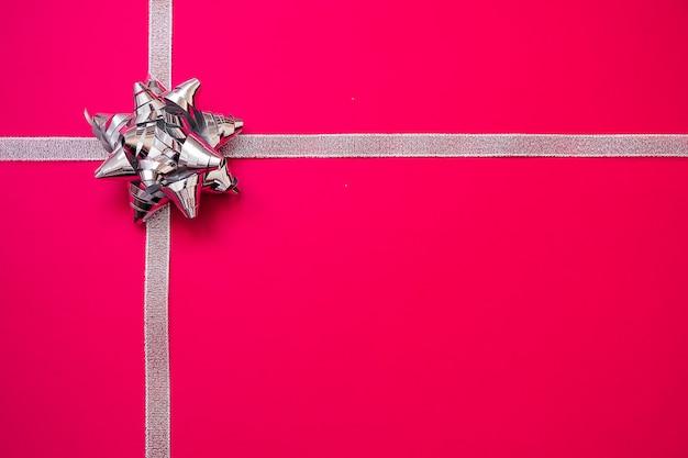 Fitas de prata com curva no fundo vermelho. conceito de presente de natal. vendas