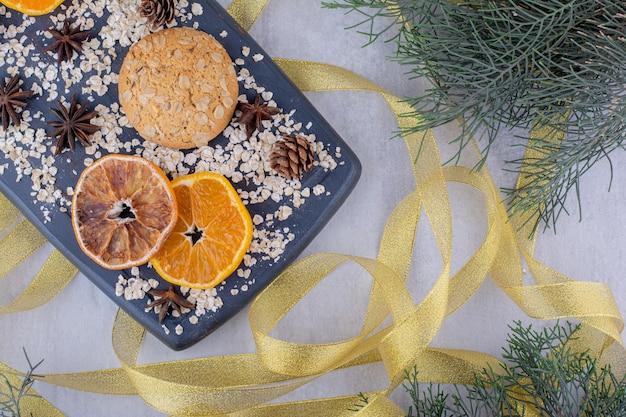 Fitas douradas em torno de uma bandeja de rodelas de laranja, biscoitos e cones de coníferas em fundo branco.