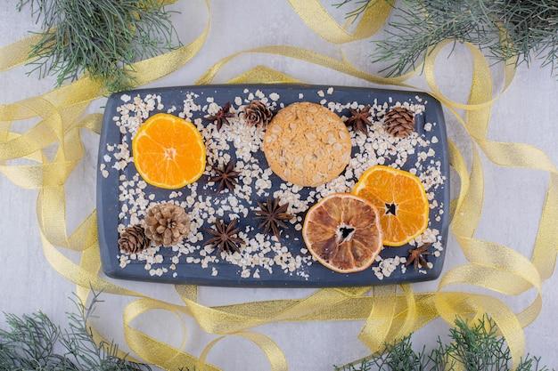 Fitas em torno de uma bandeja de rodelas de laranja, biscoitos e cones de coníferas em fundo branco.