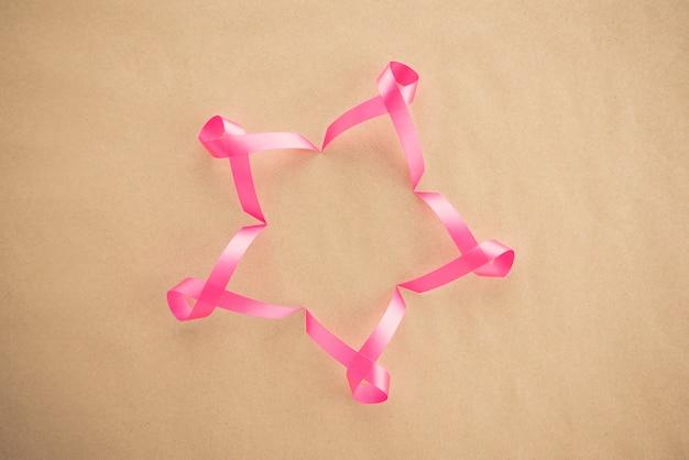 Fitas rosa cetim em papel marrom claro, símbolo de conscientização do câncer de mama