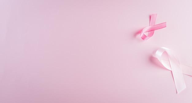 Fitas rosa em fundo pastel, símbolo da conscientização do câncer de mama feminino, cuidados de saúde e conceito médico.