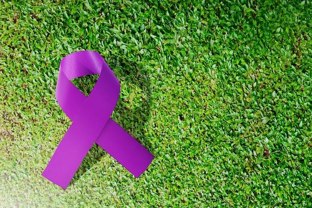 Fitas roxas em um fundo de grama verde. conceito do dia mundial do câncer
