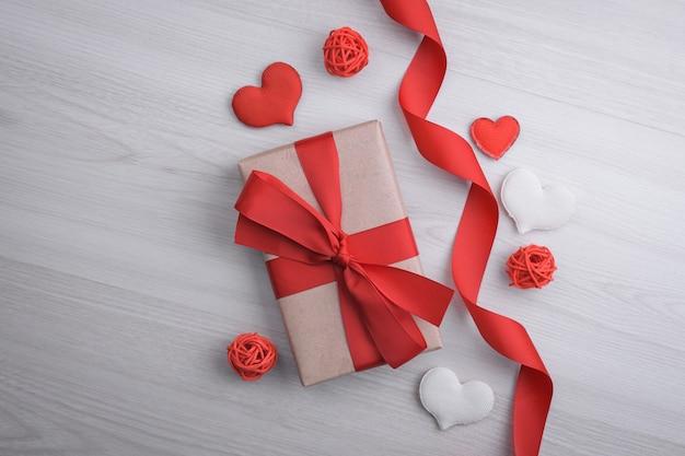 Fitas vermelhas de presente, presentes, corações em uma madeira