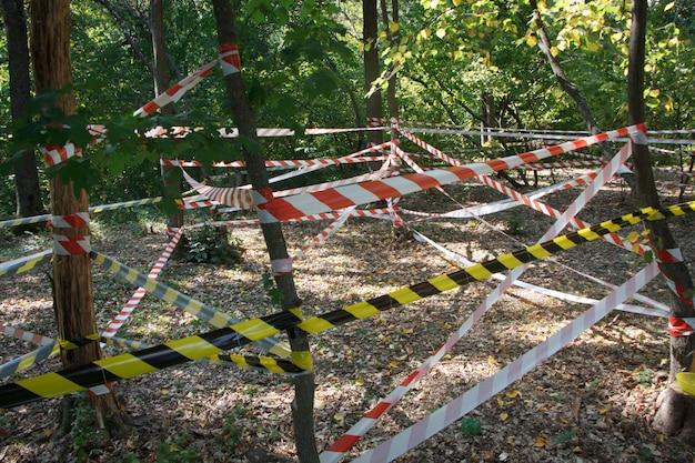 Fitas vermelhas e brancas de perigo em torno da área do incidente no parque