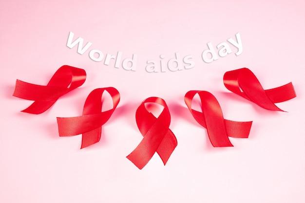 Fitas vermelhas para sinais de conscientização sobre aids na superfície rosa
