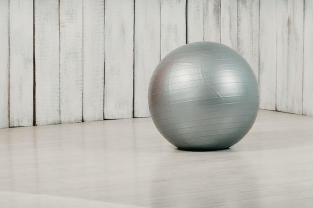 Fitball cinza em uma academia, piso leve e fundo