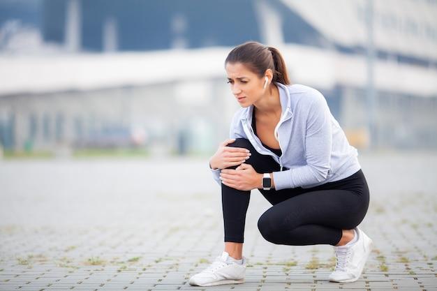 Fitness, atlético mulheres segurando o joelho com um trauma