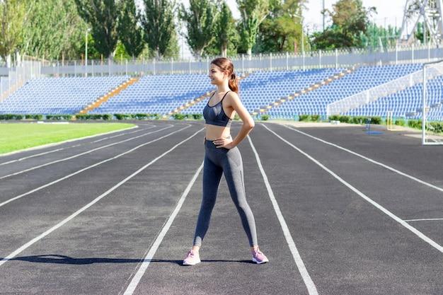 Fitness atraente mulher warm-up antes de executar na pista do estádio no dia ensolarado de verão