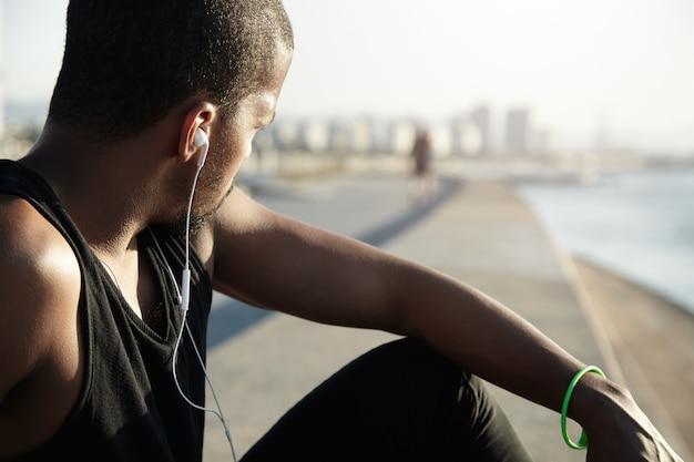Fitness e conceito de estilo de vida saudável. costas do atleta descansando após treino ao ar livre. corredor de pele escura com camiseta preta, olhando de lado, ouvindo sons meditativos nos fones de ouvido