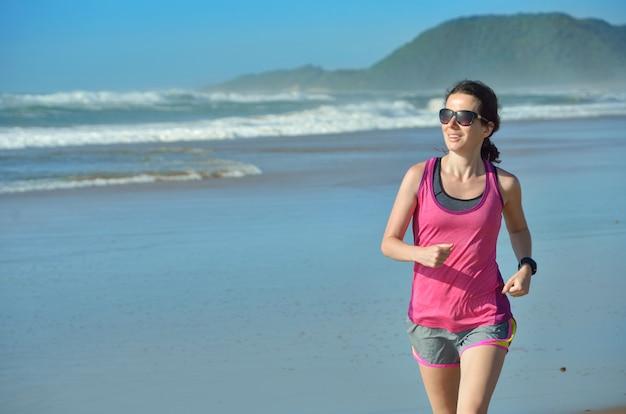 Fitness e correndo na praia, corredor de mulher feliz correndo na areia perto do mar, estilo de vida saudável e conceito de esporte