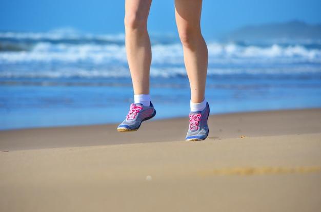 Fitness e correndo na praia, pernas de mulher corredor em sapatos correndo na areia perto do mar, estilo de vida saudável e conceito de esporte