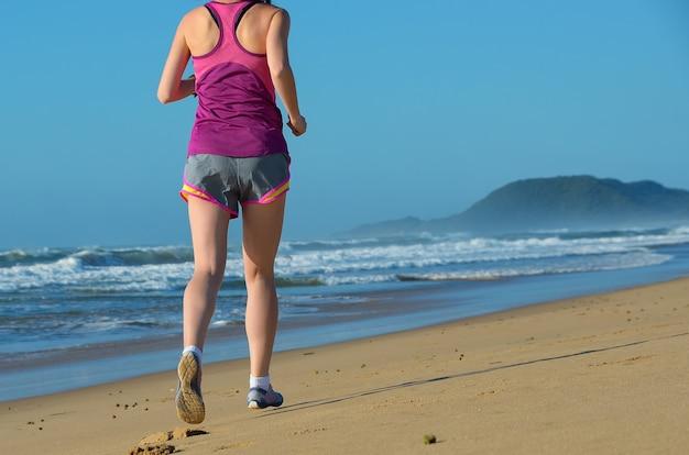 Fitness e correndo na praia, pernas de mulher corredor em sapatos na areia perto do mar, estilo de vida saudável e conceito de esporte