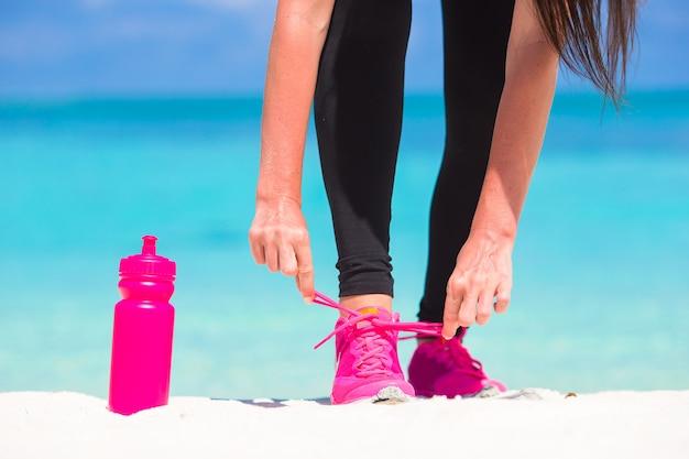 Fitness e estilo de vida saudável conceito com modelo feminino amarrar cadarços no tênis
