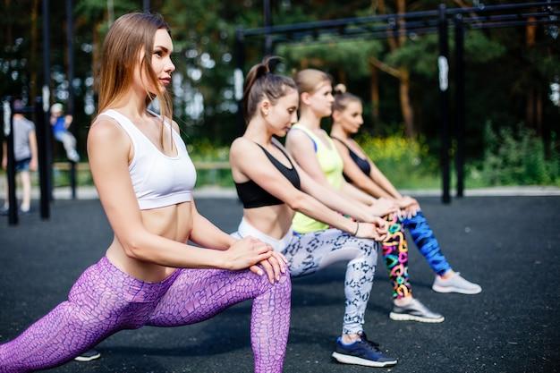 Fitness, esporte, amizade e conceito de estilo de vida saudável - grupo de mulheres jovens atraentes fazendo estocada ao ar livre