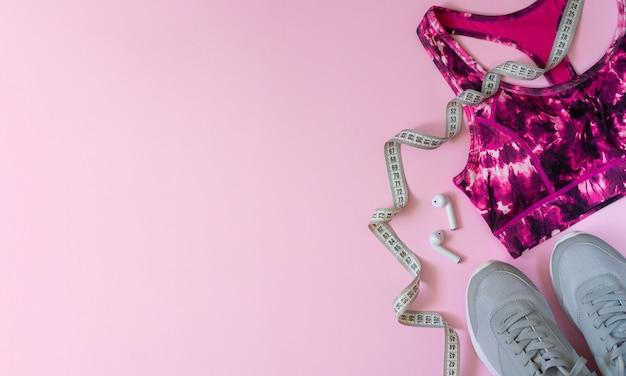 Fitness, esporte ou ioga plana leiga composição com sapatos de desporto, sutiã, fones de ouvido e fita métrica vista superior no chão rosa com copyspace